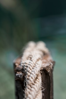 Detail eines alten ausgefransten bootsseils auf hölzernem beitrag