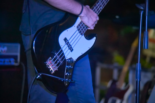 Detail eines bassisten, der seinen eacoustica-bass bei einem live-rockmusikkonzert spielt.