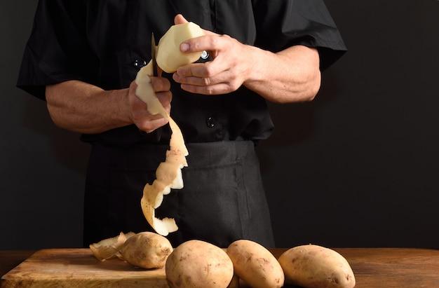 Detail eines chefs, der kartoffeln schneidet
