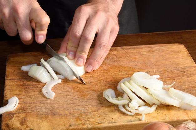 Detail eines chefs, der zwiebeln hackt