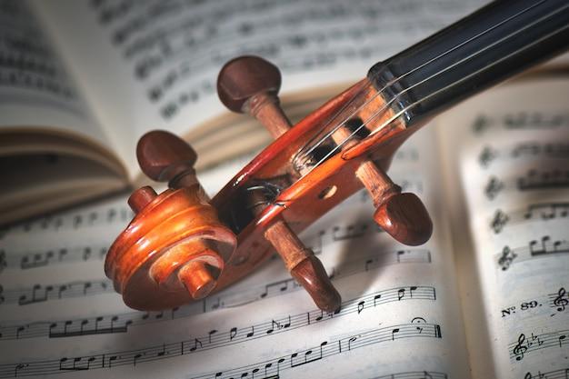 Detail eines geigengriffs, der auf einer partitur ruht