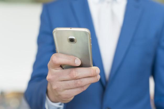 Detail eines geschäftsmannes unter verwendung ihres mobiltelefons