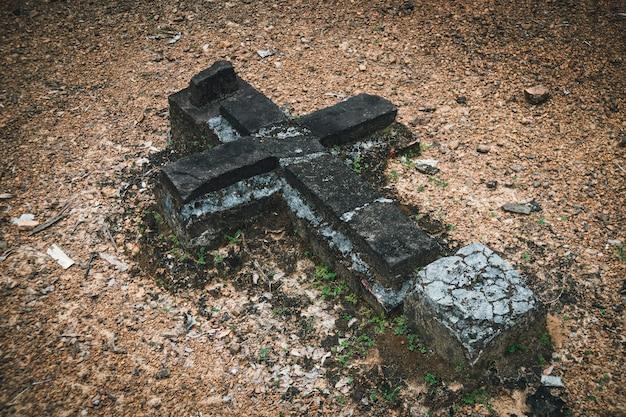Detail eines grabes auf einem friedhof. altes zerstörtes kreuz aus den grund. verlassener friedhof. katholizismus, orthodoxie, christentum