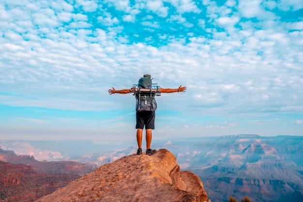 Detail eines jungen mannes mit offenen armen auf einem blickwinkel des abstiegs des south kaibab trailhead. grand canyon, arizona