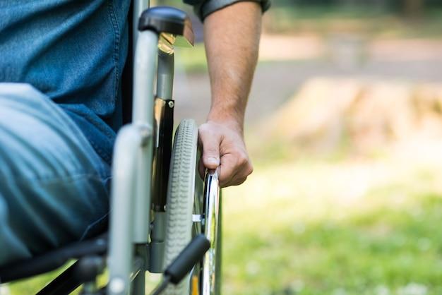 Detail eines mannes, der einen rollstuhl in einem park verwendet. copy-space auf der rechten seite