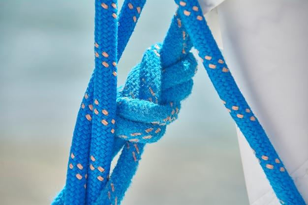 Detail eines seemannsknotens auf einem blauen ineinander verschlungenen schlüsselband