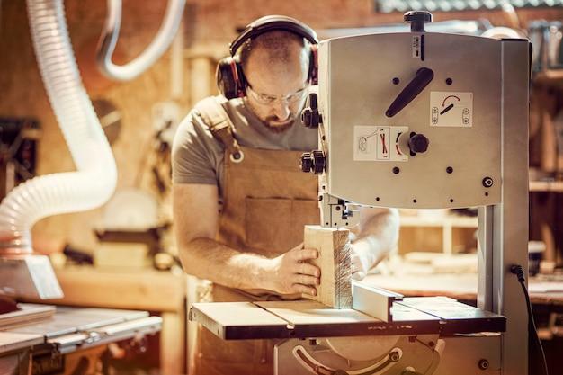 Detail eines tischlers bei der arbeit, die eine planke mit einer bandsäge in seiner werkstatt schneidet