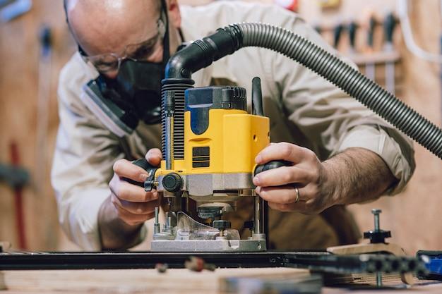 Detail eines zimmermanns, der eine fräsmaschine in seiner werkstatt benutzt