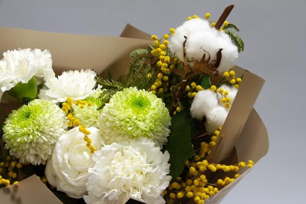 Detail nahaufnahme frühlingsstrauß von mimosenzweig, chrysantheme, ranunkel, baumwolle, nelke, selektiver fokus