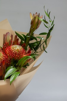 Detail nahaufnahme frühlingsstrauß von ruscus, leukadendron, leukospermum, iris, baumwolle, mimosenzweig, tulpe, selektiver fokus