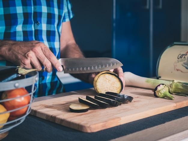 Detail von den händen, die organische auberginen auf hölzernem brett schneiden