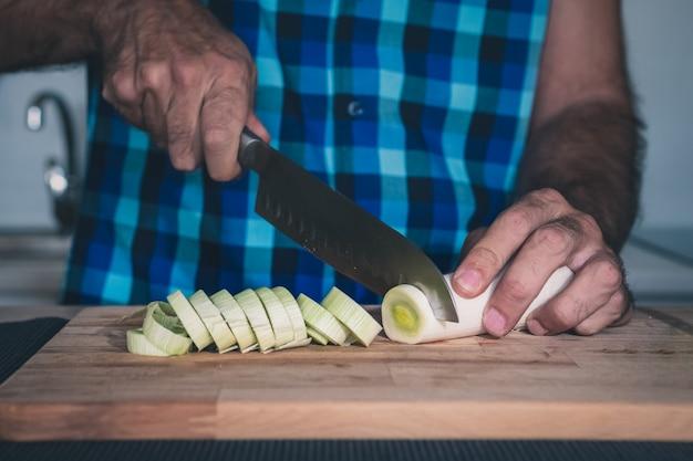Detail von den händen, die organischen porree auf hölzernem brett schneiden
