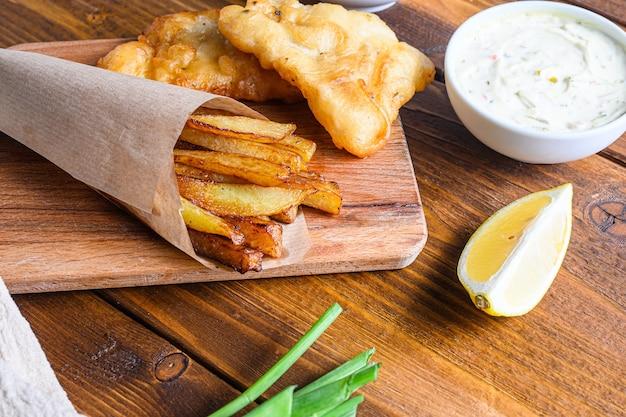 Detail von fischchips mit dip und zitrone, zerdrückten minzerbsen, tartarsauce im papierkegel