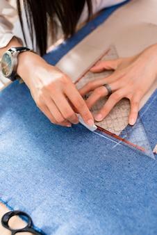 Detail von händen mit scheren am schneidershop-ausschnittstoff
