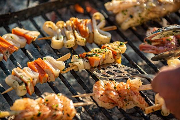 Detail von leckeren fischspießen auf dem grill mit rauch