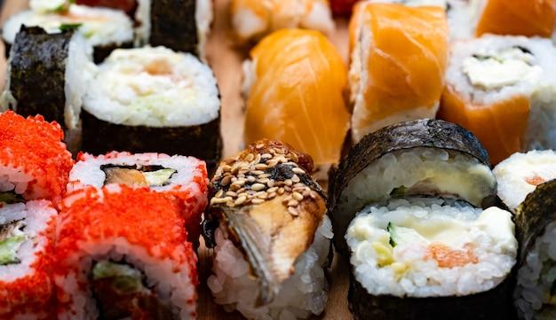 Detailansicht auf buntes set mit sushi maki und sashimi mit rohem lachs