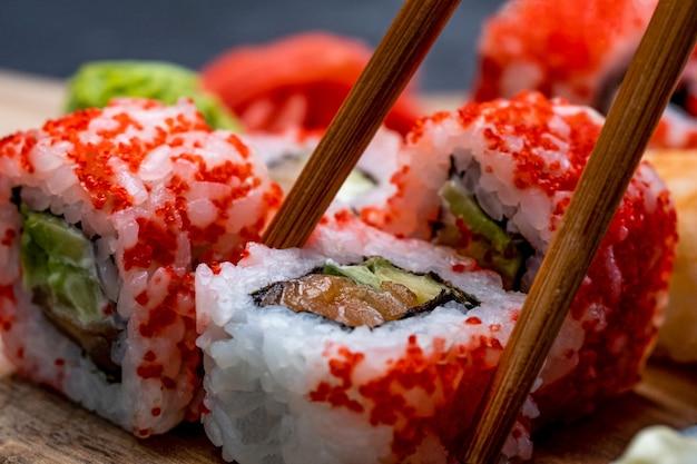 Detailansicht auf buntes set mit sushi maki und wasabi person nimmt traditionelle japanische brötchen mit ...
