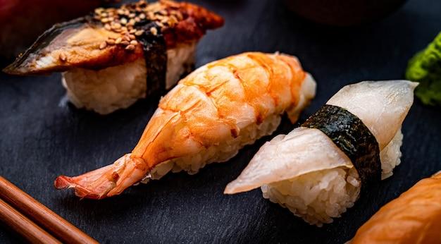 Detailansicht auf japanisches sushi-sashimi-set mit garnelen, serviert mit stäbchen und grünem wasabi...