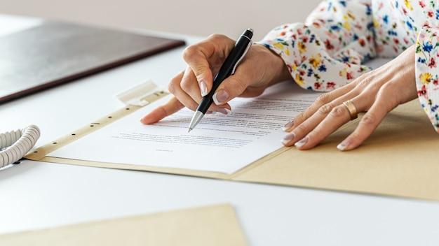 Detailansicht der geschäftsfrau korrekturlesen eines vertrags nach zeilen mit einem stift.