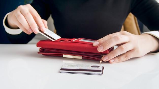 Detailansicht der jungen geschäftsfrau, die kreditkarte in ihre brieftasche steckt.