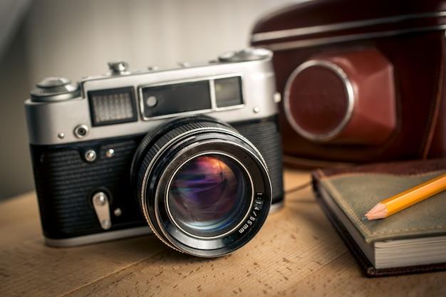 Detailansicht der klassischen filmkamera und des notebooks auf dem schreibtisch aus holz