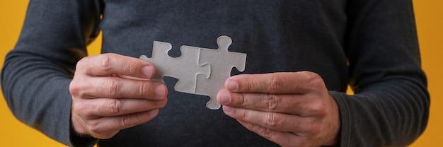 Detailansicht der männlichen hände, die zwei leere zusammenpassende puzzleteile verbinden.