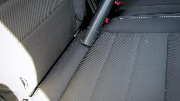 Detailansicht der reinigung des autositzes von staub mit staubsauger.