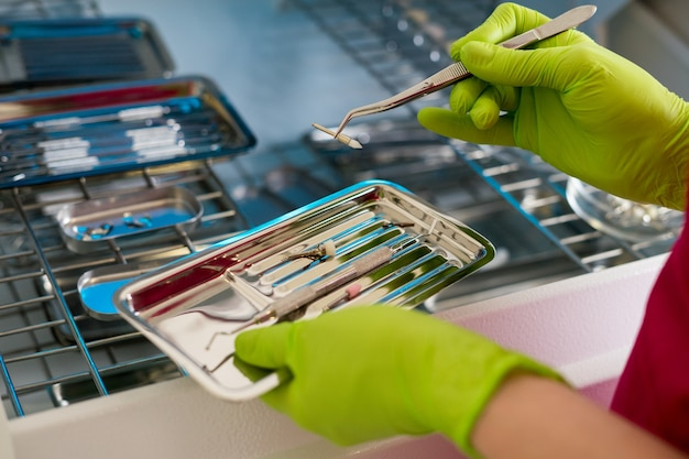 Detailansicht der zahnarzthände mit handschuhen, die zahnärztliche instrumente und verbrauchsmaterialien halten