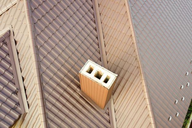 Detailansicht des daches des hauses bedeckt mit braunen metallfliesenplatten.