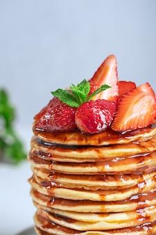 Detailansicht des hausgemachten pfannkuchenstapels mit reifen frischen roten erdbeeren, minze und sirup-topping?
