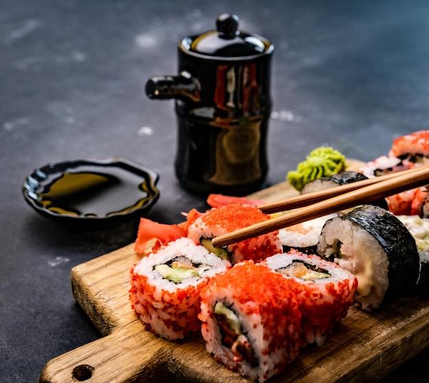 Detailansicht des sushi-maki-sets, serviert auf holztablette mit sojasauce in schüssel und person, die hand hält...