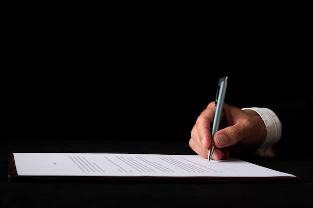 Detailansicht einer hand eines geschäftsmannes, der ein dokument oder einen vertrag unterzeichnet. auf schwarzem hintergrund.