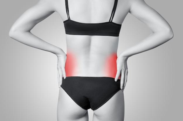 Detailansicht einer jungen frau mit nierenschmerzen auf grauem hintergrund. schwarzweißfoto mit rotem punkt.