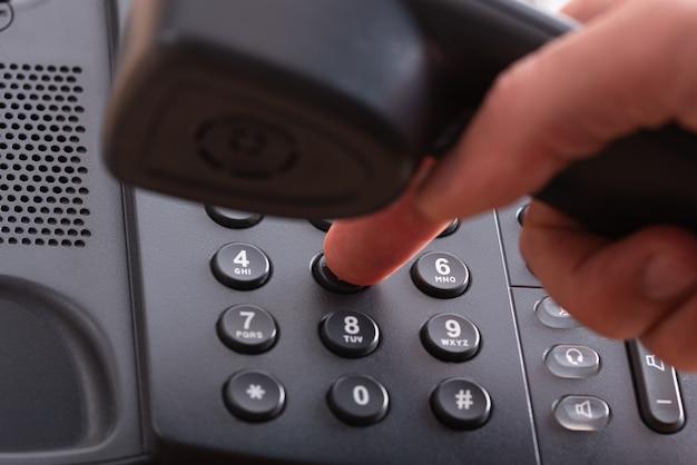 Detailansicht eines fingers, der eine telefonnummer am schwarzen festnetztelefon wählt.