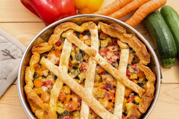 Detailansicht eines veganen gemüsekuchens wellness und ernährung alle zutaten auf einem holztisch