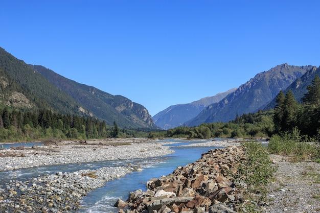 Detailansicht flussszenen in den bergen des nationalparks dombai, kaukasus, russland, europa. sommerlandschaft, sonnenscheinwetter, dramatischer blauer himmel und sonniger tag