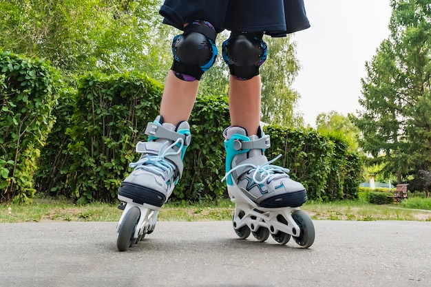 Detailansicht von weißen rollschuhen oder rollerblading. rollschuhbeine eines kindes im park. mädchenbeine in rollerblades.