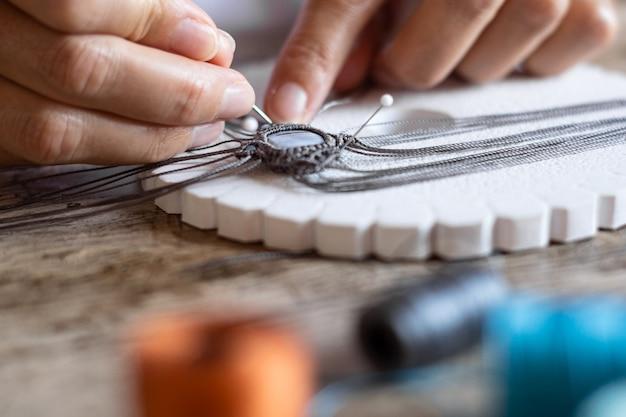 Detaillierte makro-nahaufnahme der frauenfinger, die an einem handgemachten geknoteten mikro-makramee-armband mit unscharfen garnrollen im bokeh-effekt arbeiten