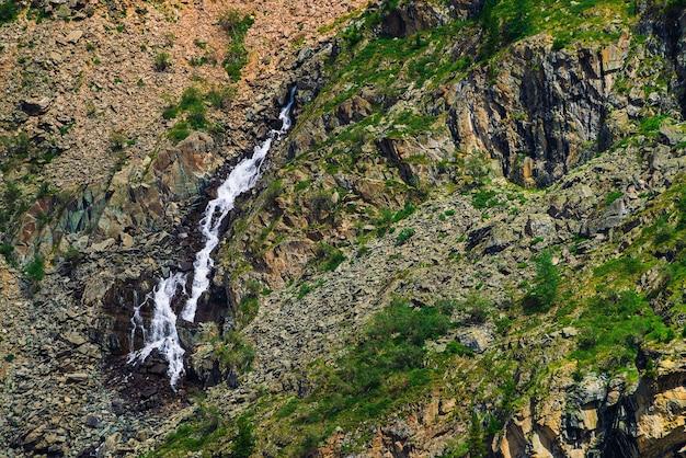 Detaillierte natürliche textur der neigung von losen steinen. gebirgswasserstrom fließt den berghang hinunter.