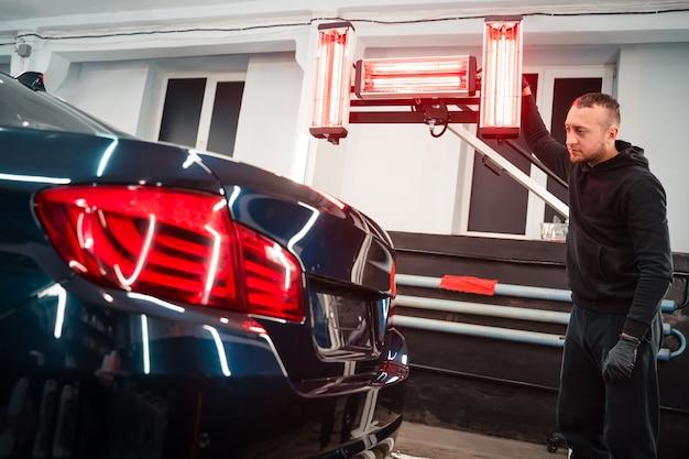 Detaillierter arbeiter mit infrarotlampen in der nähe des autos.