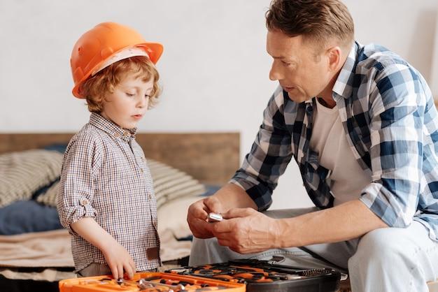 Details besprechen. attraktives kind, das helm-berührungsbox mit werkzeugen trägt, während es aufmerksam nach unten schaut