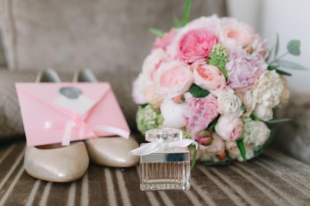 Details der braut: schuhe, rosafarbener blumenstrauß, parfüme und einladungen.