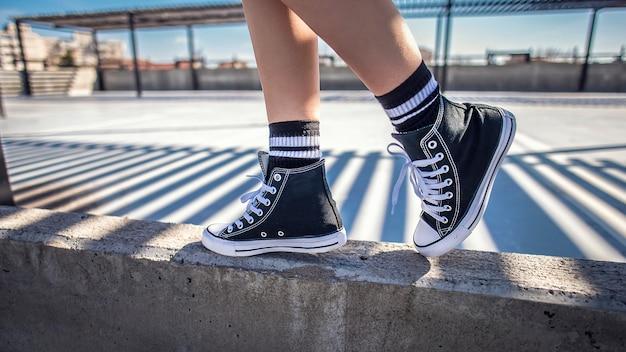 Details der frau beine zu fuß auf beton leiste in ihren klassischen sneakers