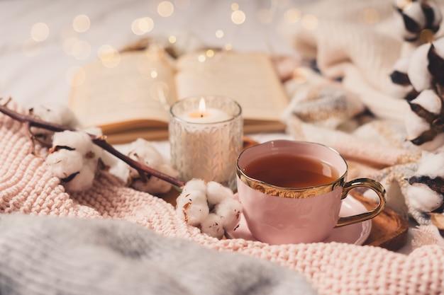 Details des stilllebens im wohnraum des wohnzimmers. pullover, tasse tee, baumwolle, gemütlich, buch, kerze