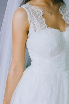 Details eines hochzeitskleides. nahaufnahme des gesichtslosen mädchens im schönen weißen hochzeitskleid. brautzubehör.