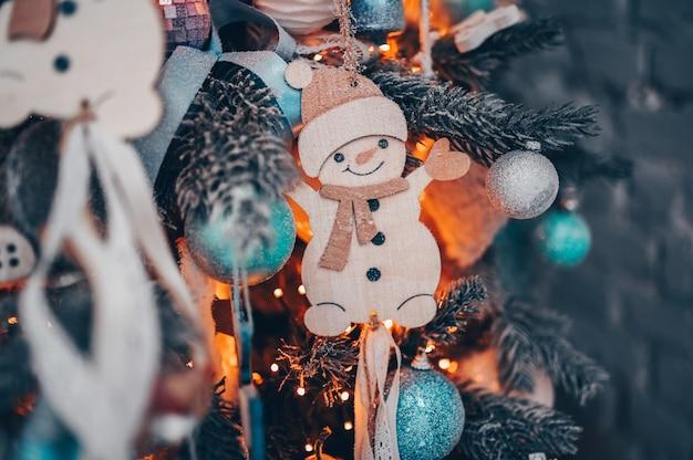 Details eines weihnachten verzierten baums im dunklen türkis und in den orange farben mit spielzeugschneemann