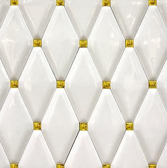 Detailtextur aus weißen keramikfliesen mit goldenen akzenten. hintergrund, textur