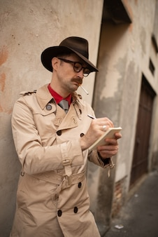 Detektiv schreibt auf einem notizbuch, während er an einer alten mauer steht