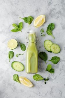 Detox-getränk in glasflasche mit frischen obst- und gemüsezutaten. spinat-smoothie, gesundes, sauberes esskonzept.