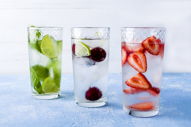 Detox-getränk mit erdbeere, limette, kirsche und minze. verschiedene sommerlimonaden oder eistee. mojito-cocktails mit eiswürfeln.